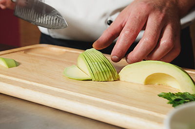 chef cutting avocado on table